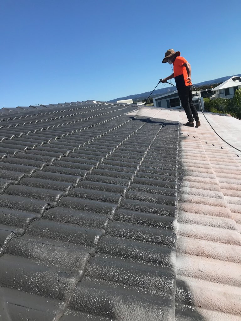 man roof cleaning by pressured water